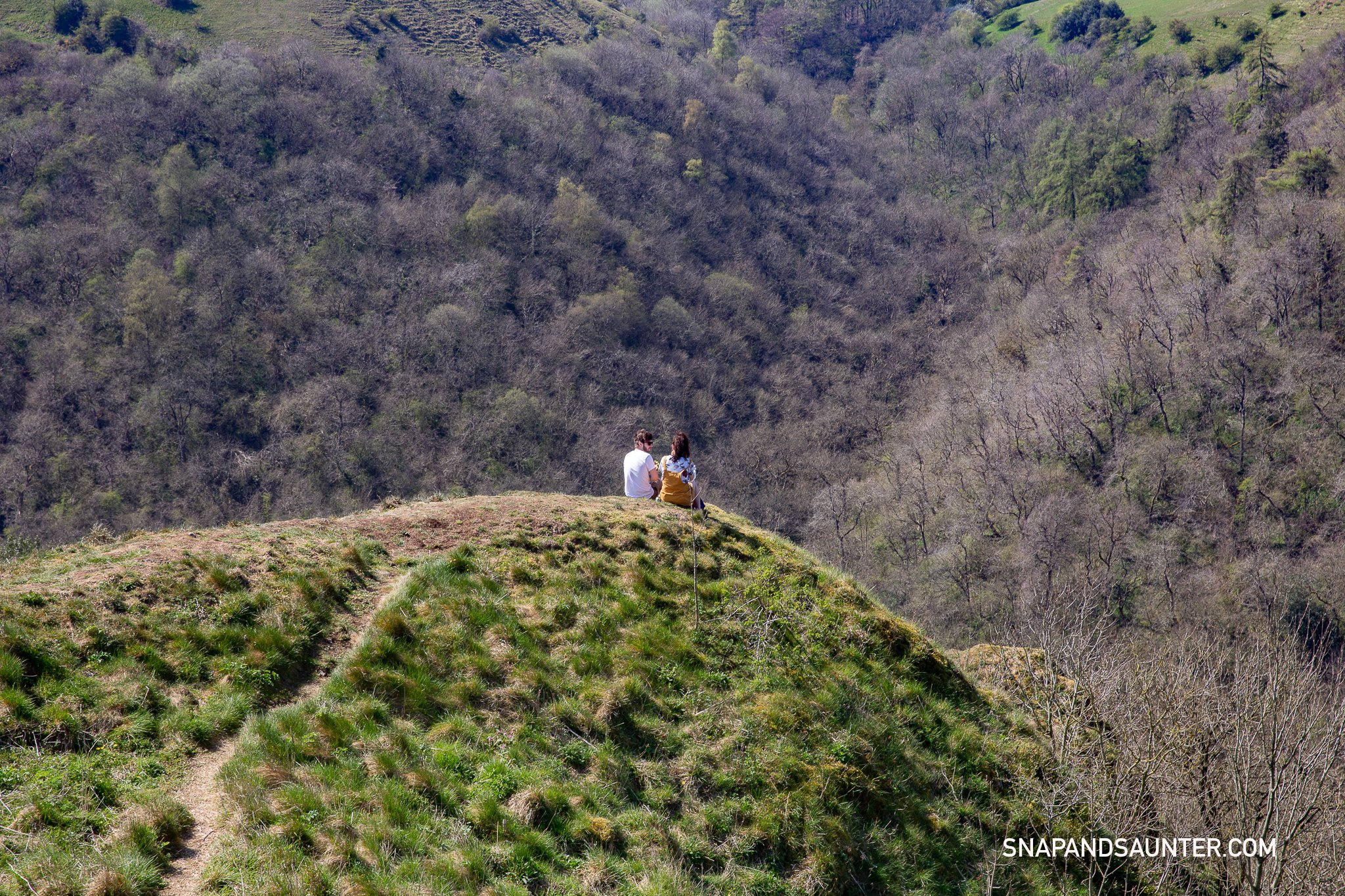 A couple sitting on top of Thor's Cave enjoying the views of Manifold Valley.