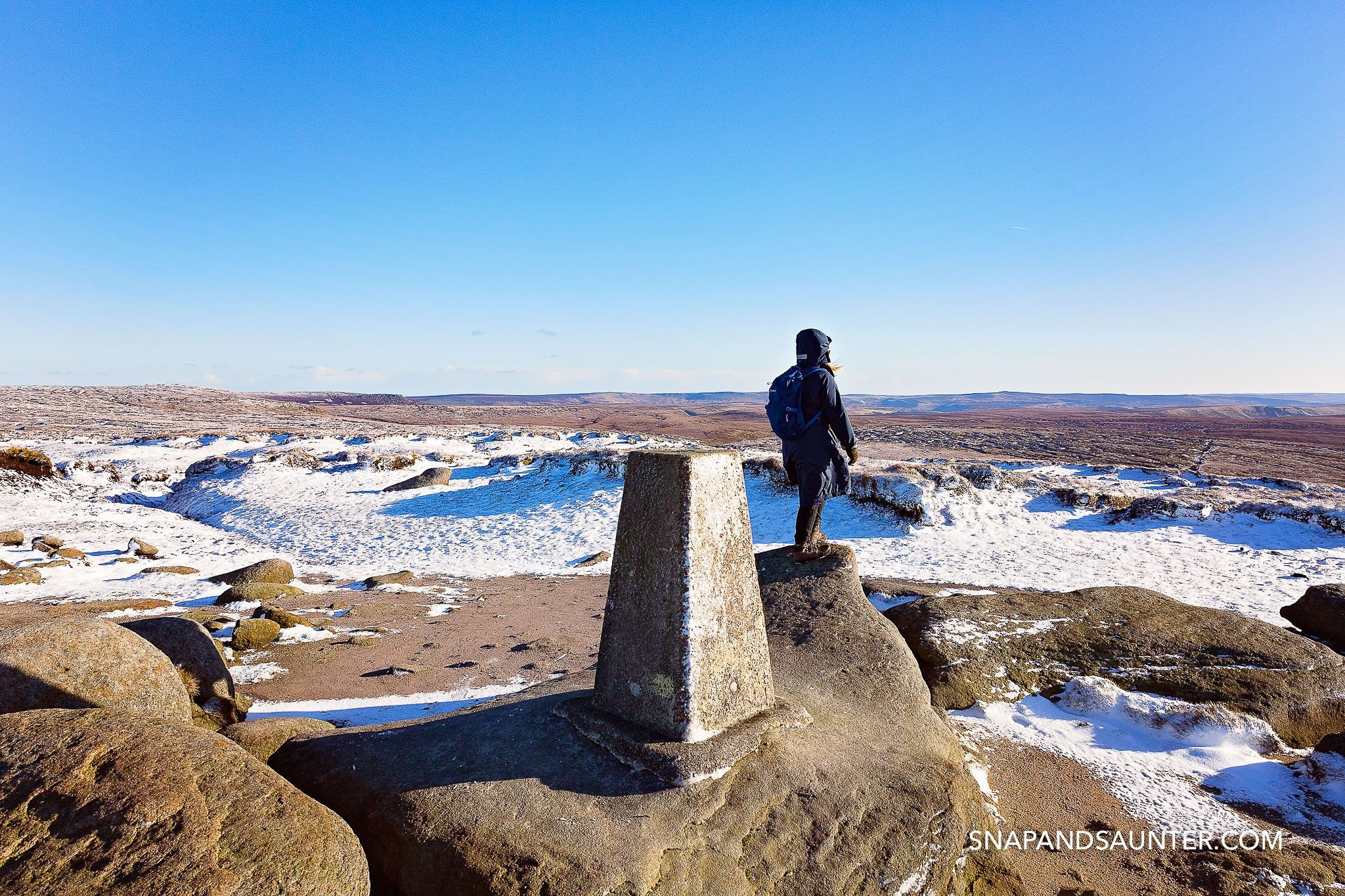 Looking out at the countryside at the trig point at Higher Shelf Stone summit in winter in Bleaklow in Derbyshire