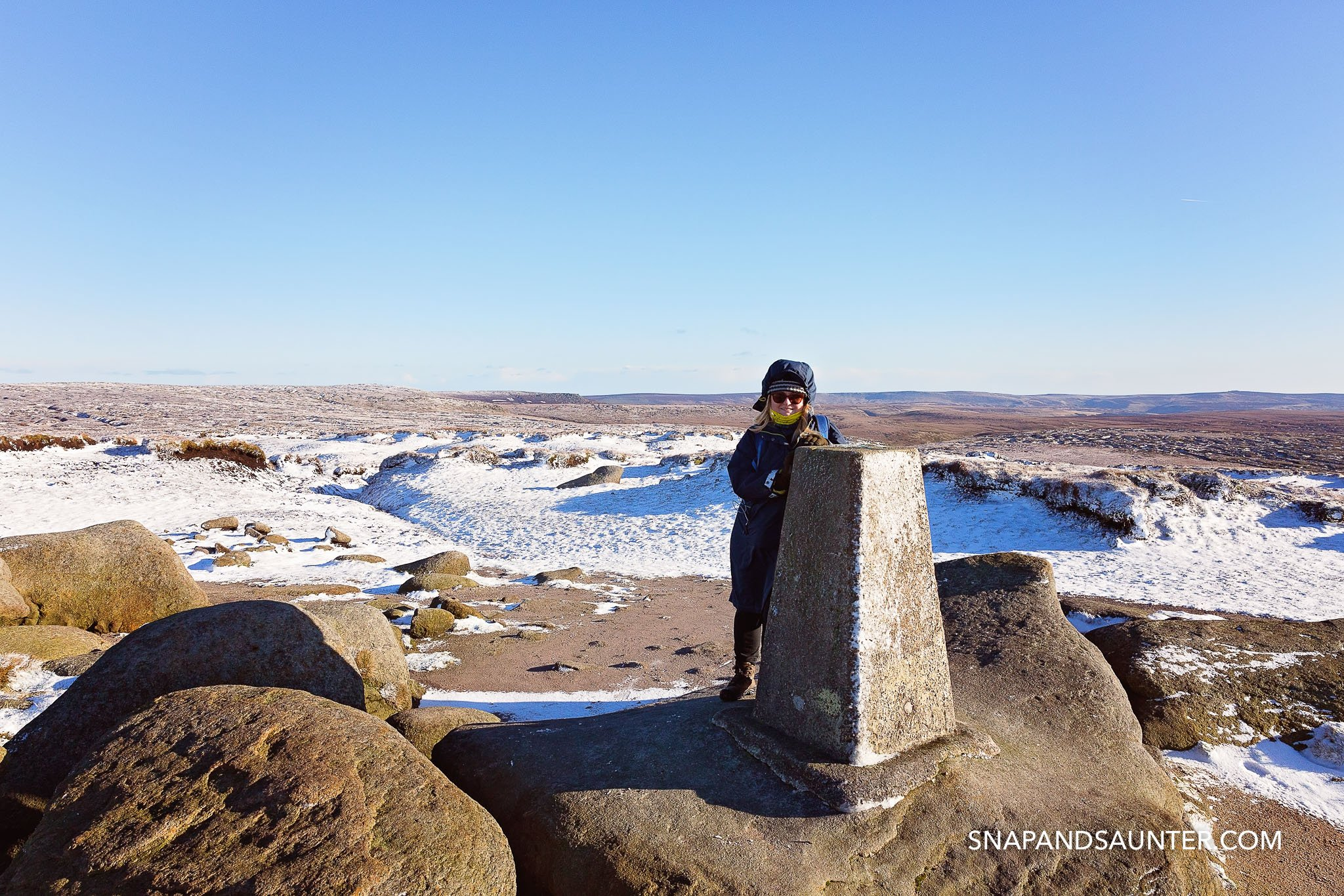A woman in sunglasses all wrapped up in winter standing next to a trig point at Higher Shelf Stone summit at Bleaklow in Derbyshire