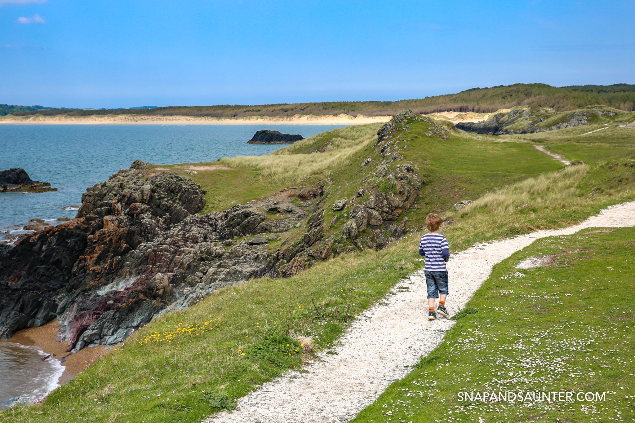 A boy walking towards Llandwyn Island in Anglesey in Wales