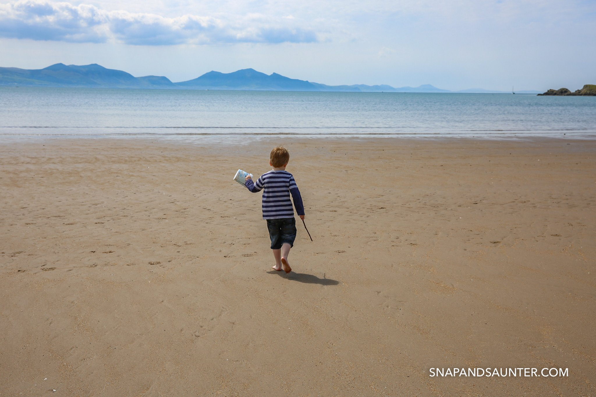 A child running on the beach with bucket and stick