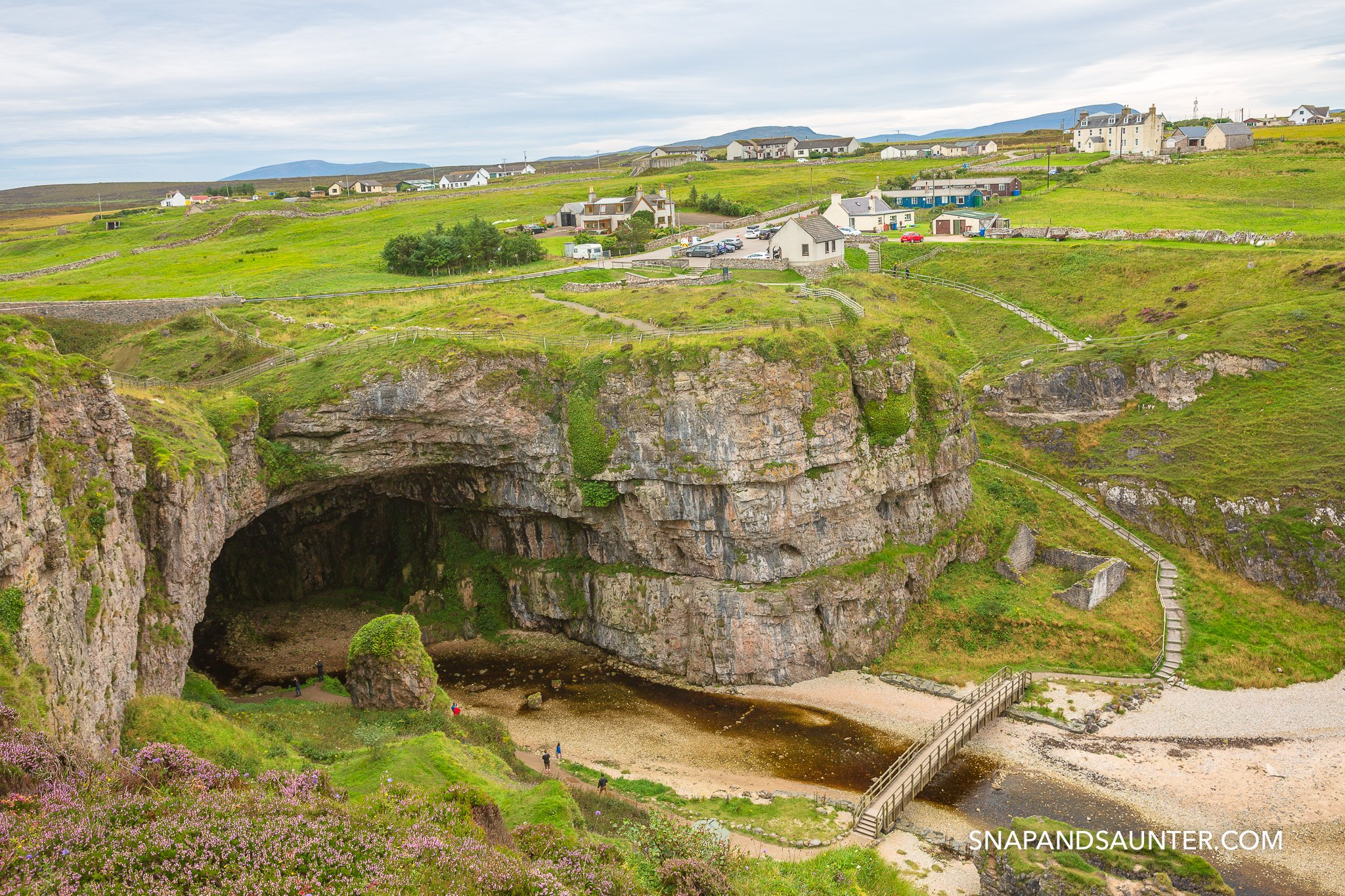 A view of Smoo Cave entrance with houses on top near Durness on the North Coast 500
