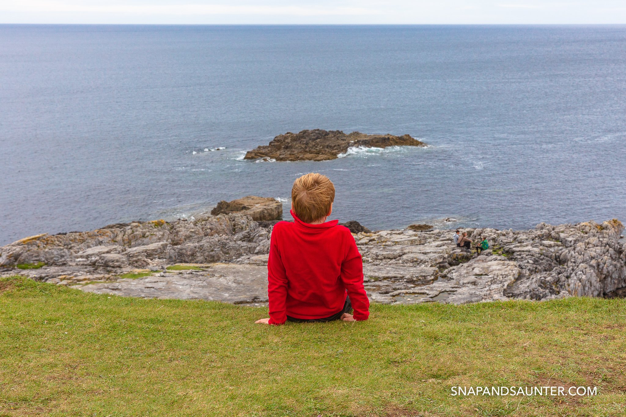 A boy sitting on grass watching the sea