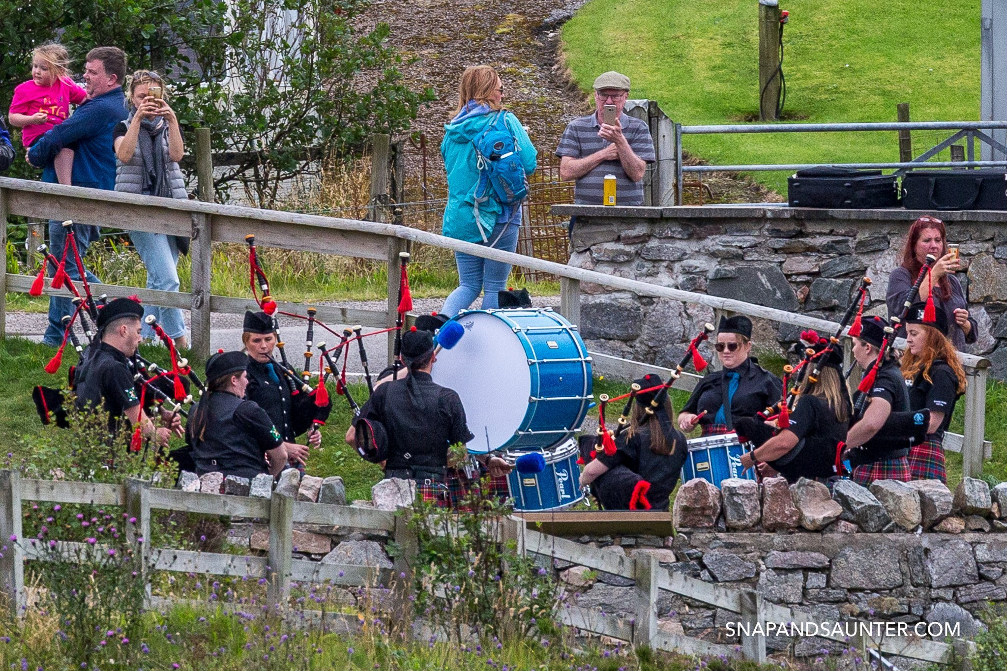 Scottish pipers band playing at the Smoo cave with people taking photos of them