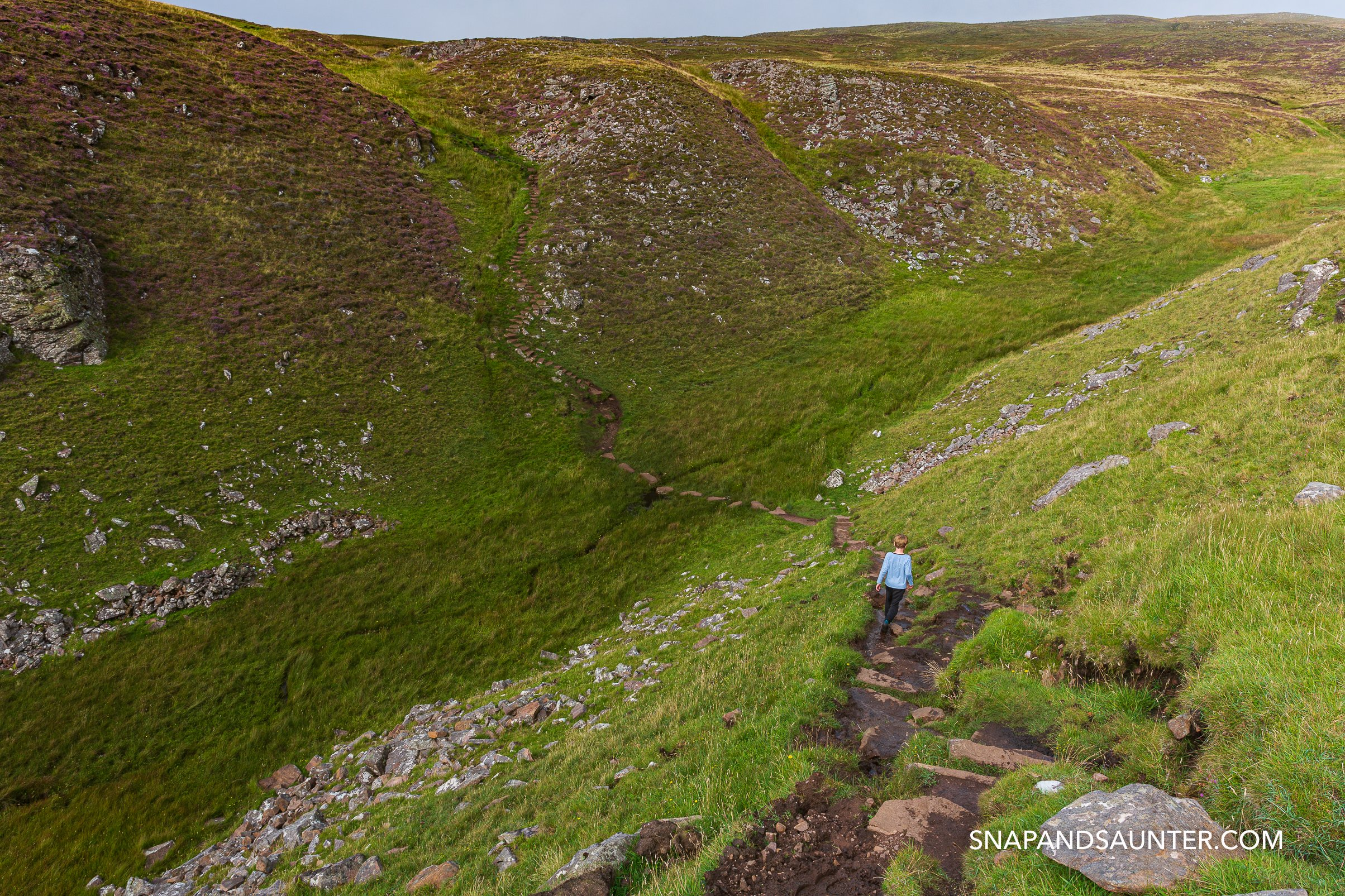a child walking in the landscape towards the Old Man of Stoer on the North Coast 500