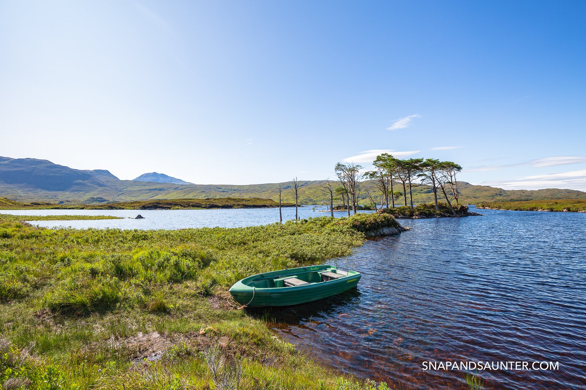 Little Island with trees and a dingy on Loch Assynt on route North Coast 500