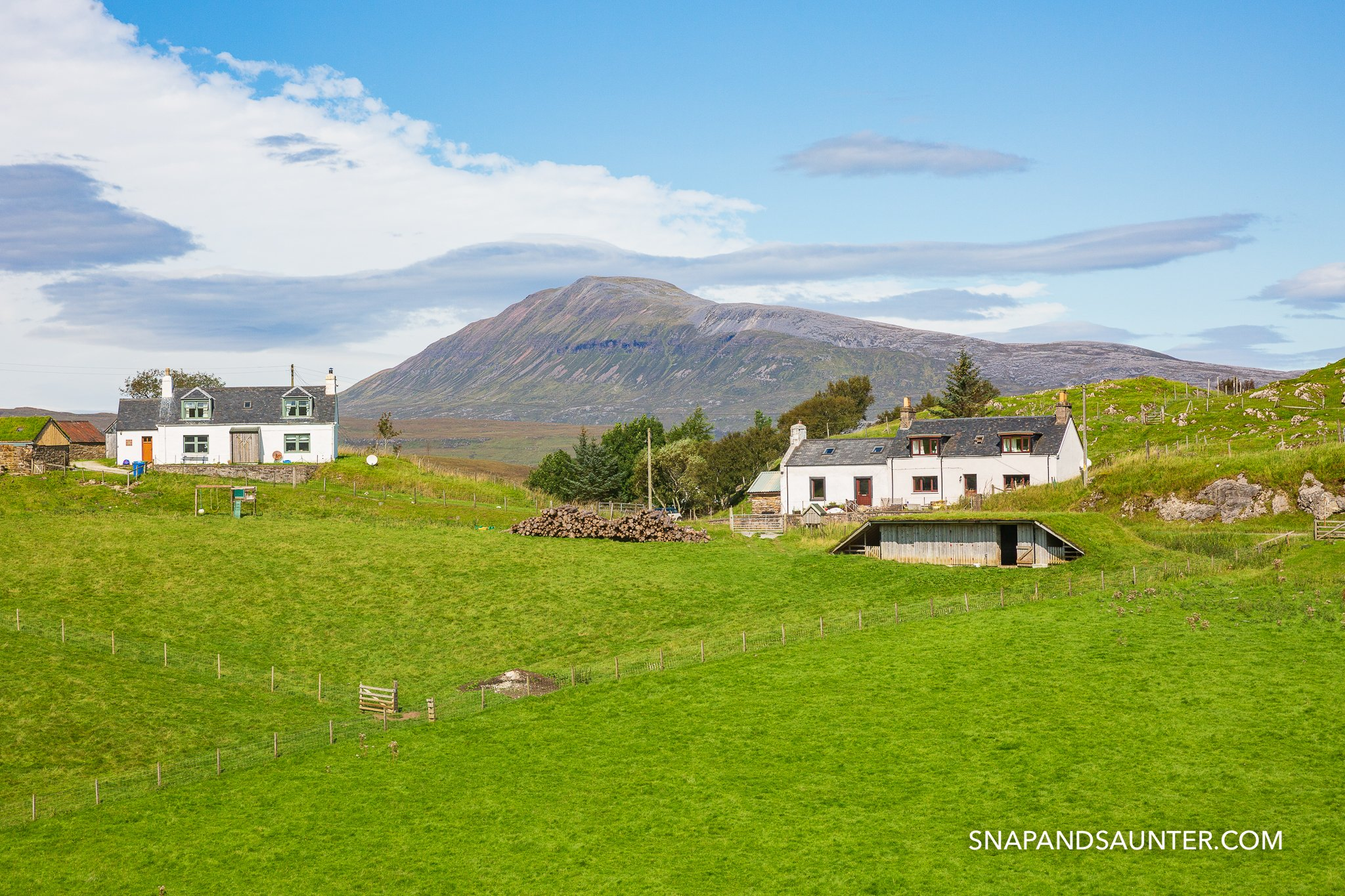 Houses with mountains background along the Loch Assynt on route North Coast 500