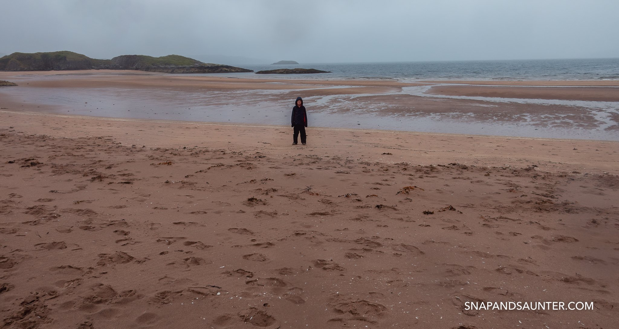 A boy standing on Gairloch Beach in the rain